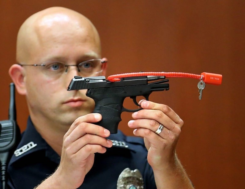 Sanford police officer Timothy Smith holds up the gun that was used to kill Trayvon Martin, while testifying in the George Zimmerman trial. (AP Archive Photo)