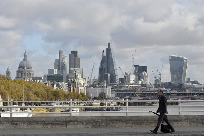 A man crosses Waterloo Bridge with the backdrop of the City of London and the financial district in London.