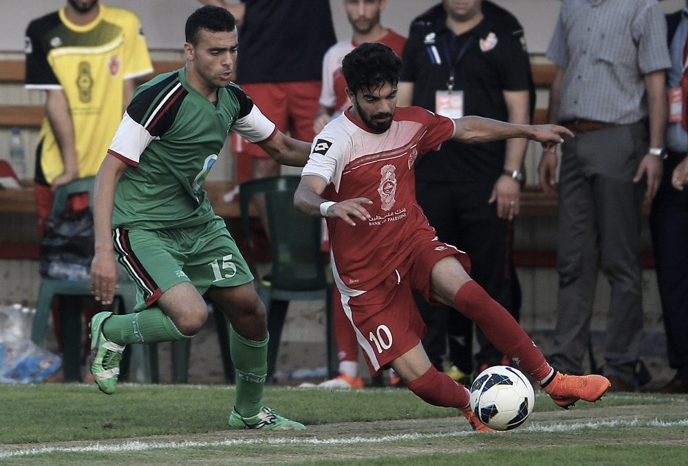 Palestinian Ahli al-Khalil player Fadi Zeidan (R) and Itihad Al-Shejaeiya player Mustafa Hasaballah (L) fight for the ball during a football match between the Ahli al-Khalil and Itihad Al-Shejaeiya in Al Yarmouk stadium in Gaza City.