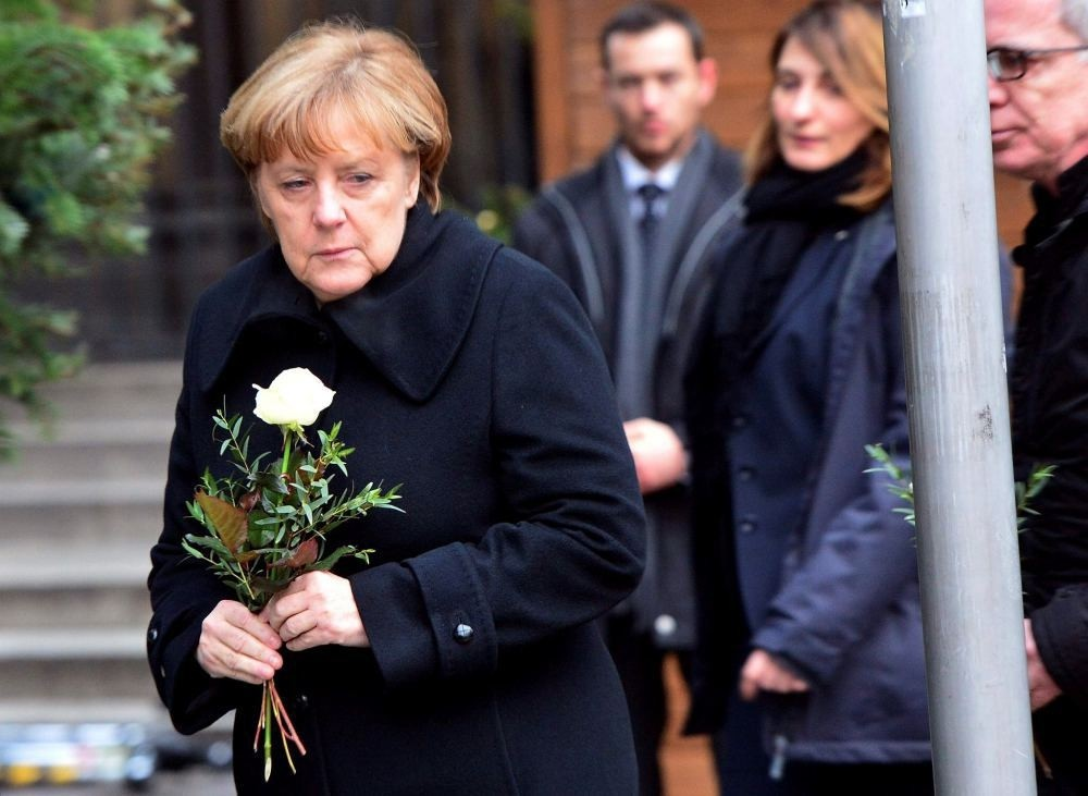 German Chancellor Angela Merkel lays flowers with German Interior Minister Thomas de Maiziere on Dec. 20 at the site where a truck crashed into a Christmas market near the Kaiser-Wilhelm-Gedaechtniskirche.