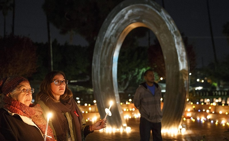 Visitors gather with candles near a memorial stainless steel arch during a World AIDS Day event at the Las Memorias AIDS Monument in Los Angeles, California USA, 01 December 2016 (EPA Photo)