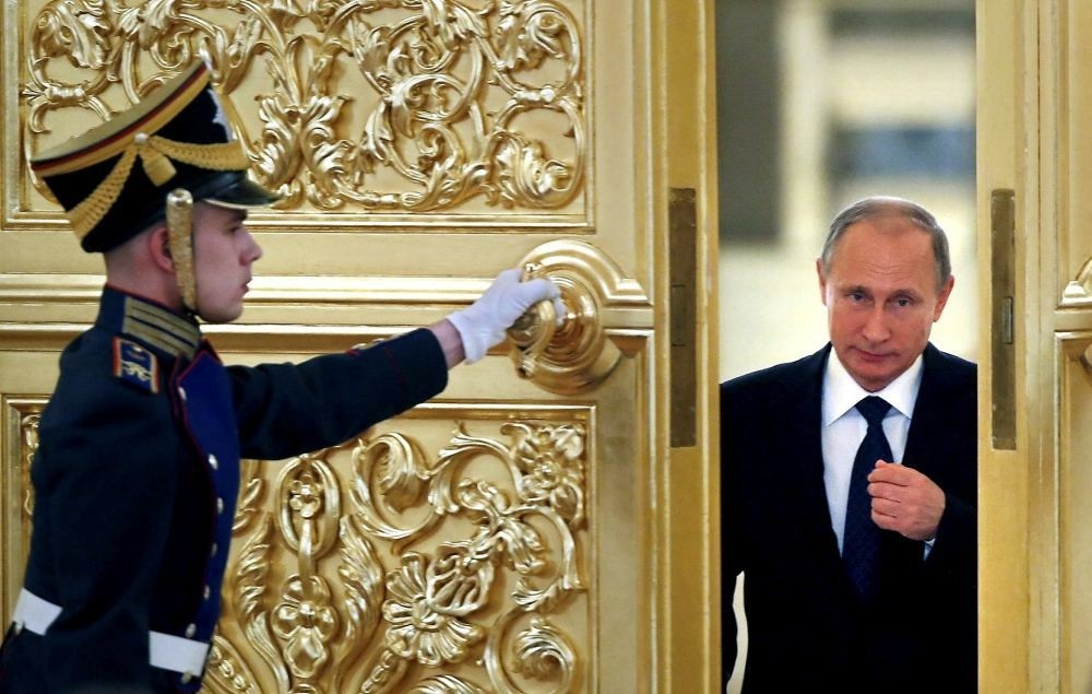An honor guard opens the door as Russian President Vladimir Putin enters a hall at the Kremlin in Moscow.