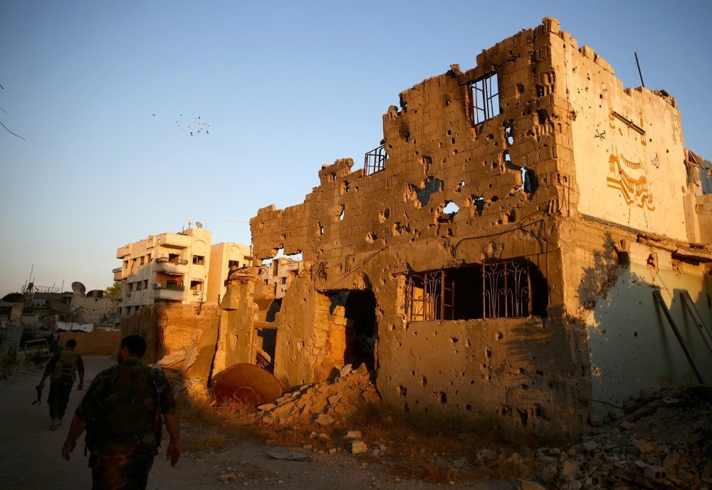 Free Syrian Army soldiers walking past damaged buildings in moderate-held Jobar, a suburb of Damascus, Syria, Sept. 6.