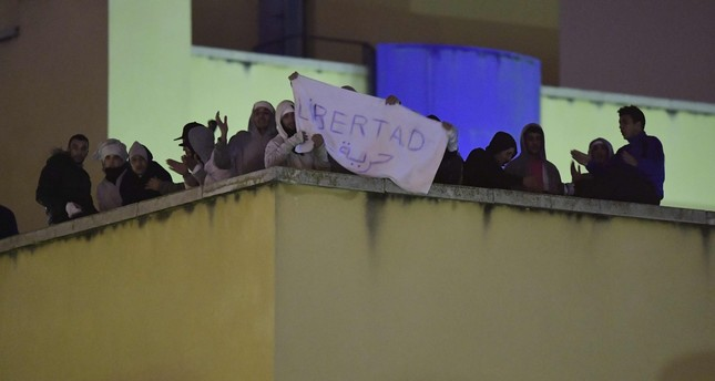 Refugees protest against the conditions in the detention center on the roof of the Immigration Detention Center (CIE), Oct. 19, 2016, Madrid. (AFP Photo)