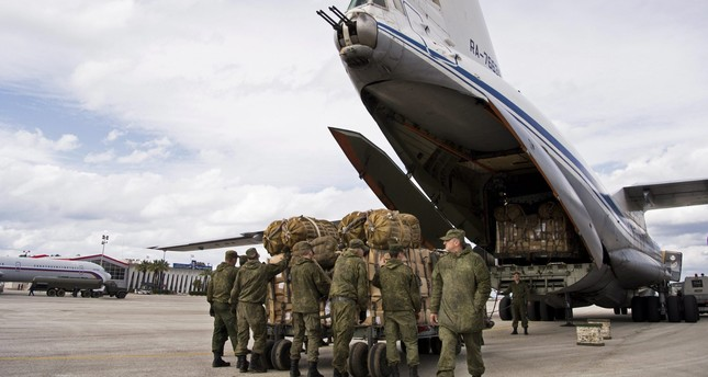 Russian air force personnel prepare to load humanitarian cargo on board a Syrian Il-76 plane at Hemeimeem air base in Syria. (AP Photo)