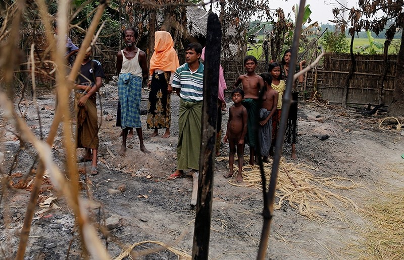 A family stands beside remains of a market, which was set on fire in Rohingya village, outside Maungdaw in Rakhine state, Myanmar October 27, 2016. (Reuters Photo)