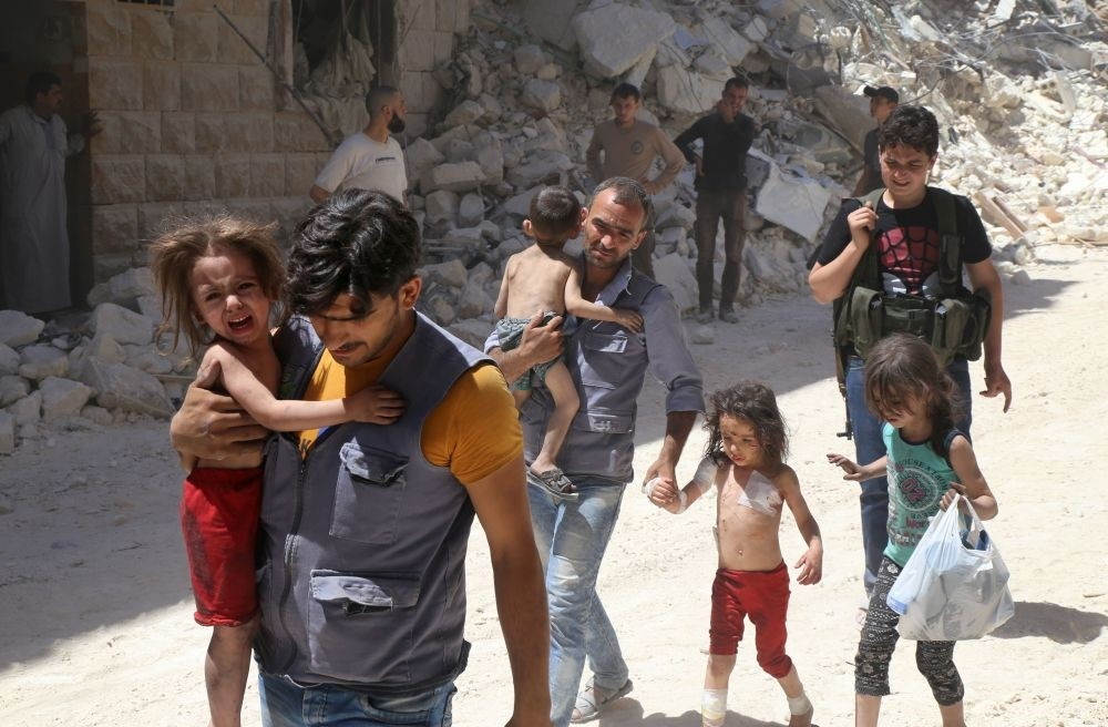 Syrian men carry injured children amid the rubble of destroyed buildings following reported airstrikes on the opposition-held neighborhood of al-Mashhad in the northern city of Aleppo on July 25.