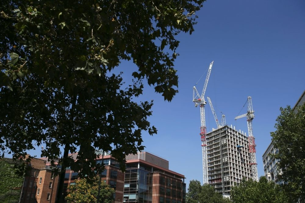 A picture shows cranes next to a block of flats under development in London on August 17.