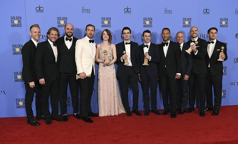 The cast and crew of ,La La Land, poses in the press room with the award for best motion picture - musical or comedy at the 74th annual Golden Globe Awards (AP Photo)