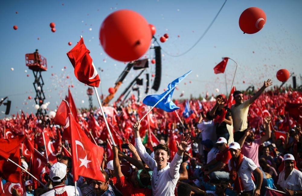 People waving flags as they stand in front of giant screens next to balloons in the color of the Turkish national flag in Istanbul at the Democracy and Martyrs Rally against the July 15 coup attempt, Aug. 7.