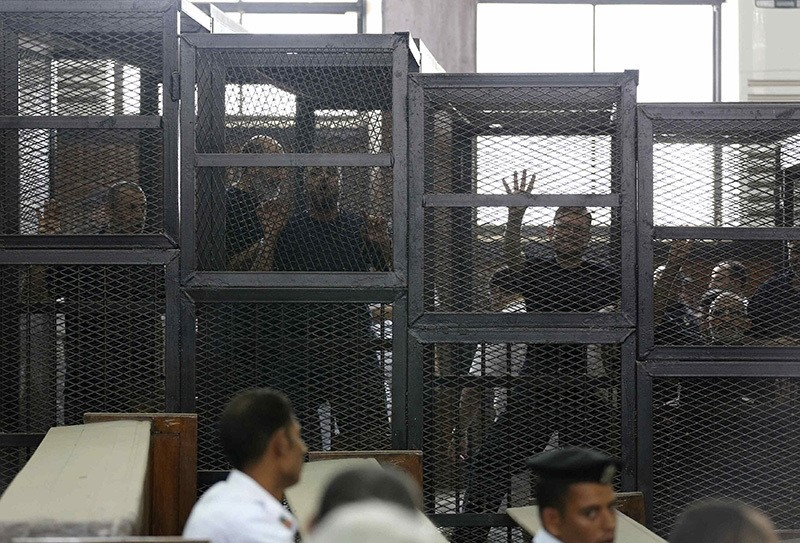 Muslim Brotherhood's General Guide Mohamed Badie (R) is pictured in a defendant's cage with other defendants in a courtroom in Cairo June 7, 2014. (Reuters Photo)