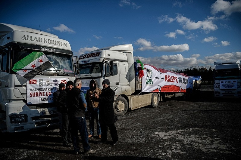 People stay next to an aidu00a0convoy to Aleppo organized by the IHH Humanitarian Relief Foundation about to leave, Dec. 14, 2016, Istanbul. (AFP Photo)u00a0