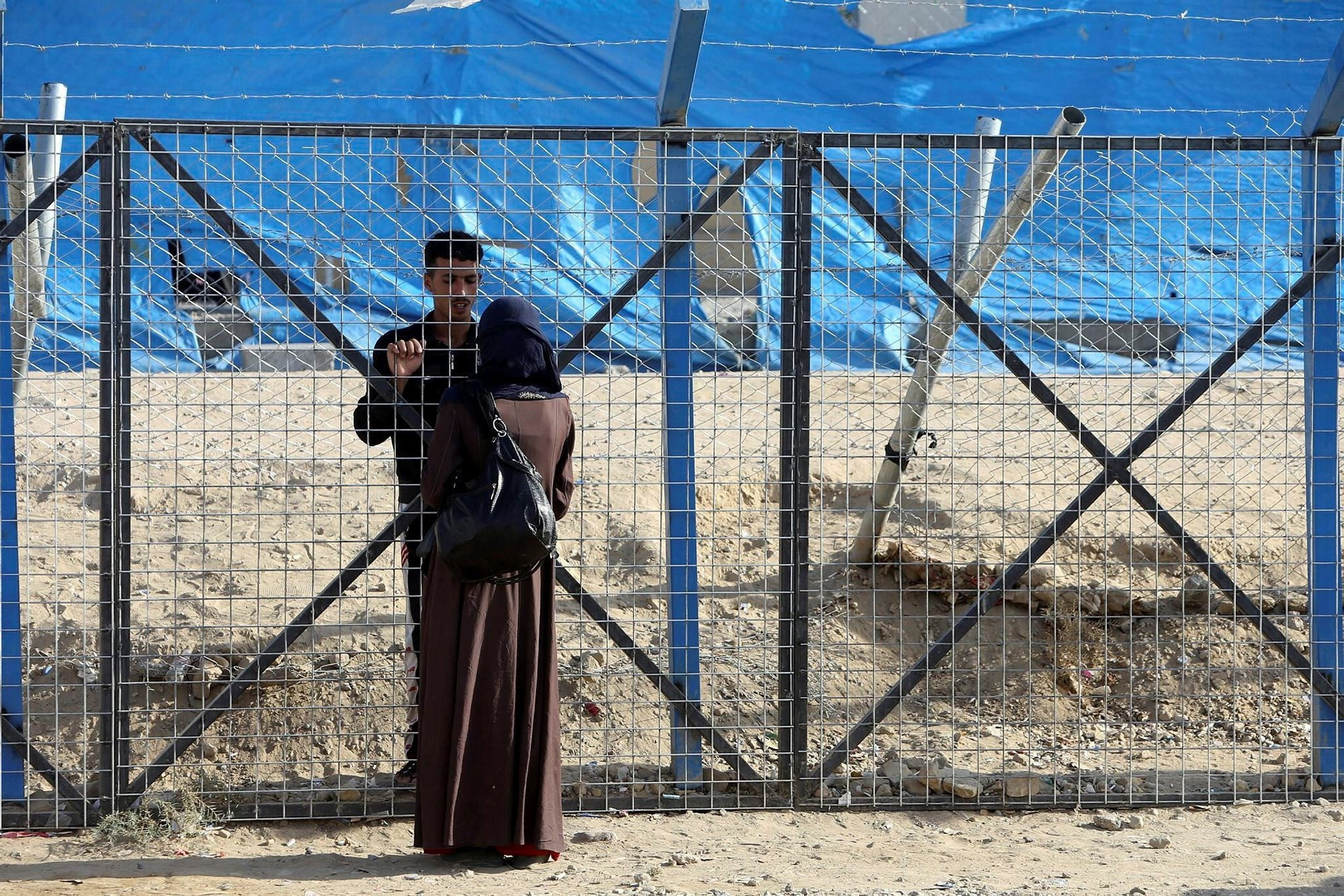 A displaced woman who fled Daesh militants from Mosul speaks with her husband through a fence at Deepaka camp in the northwest of Erbil, Iraq, October 20, 2016. (Reuters Photo)