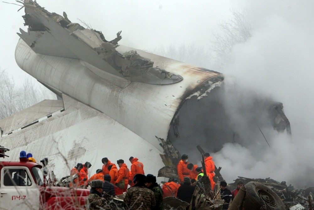 Crews at the scene of the plane crash inspect the debris of the fuselage.