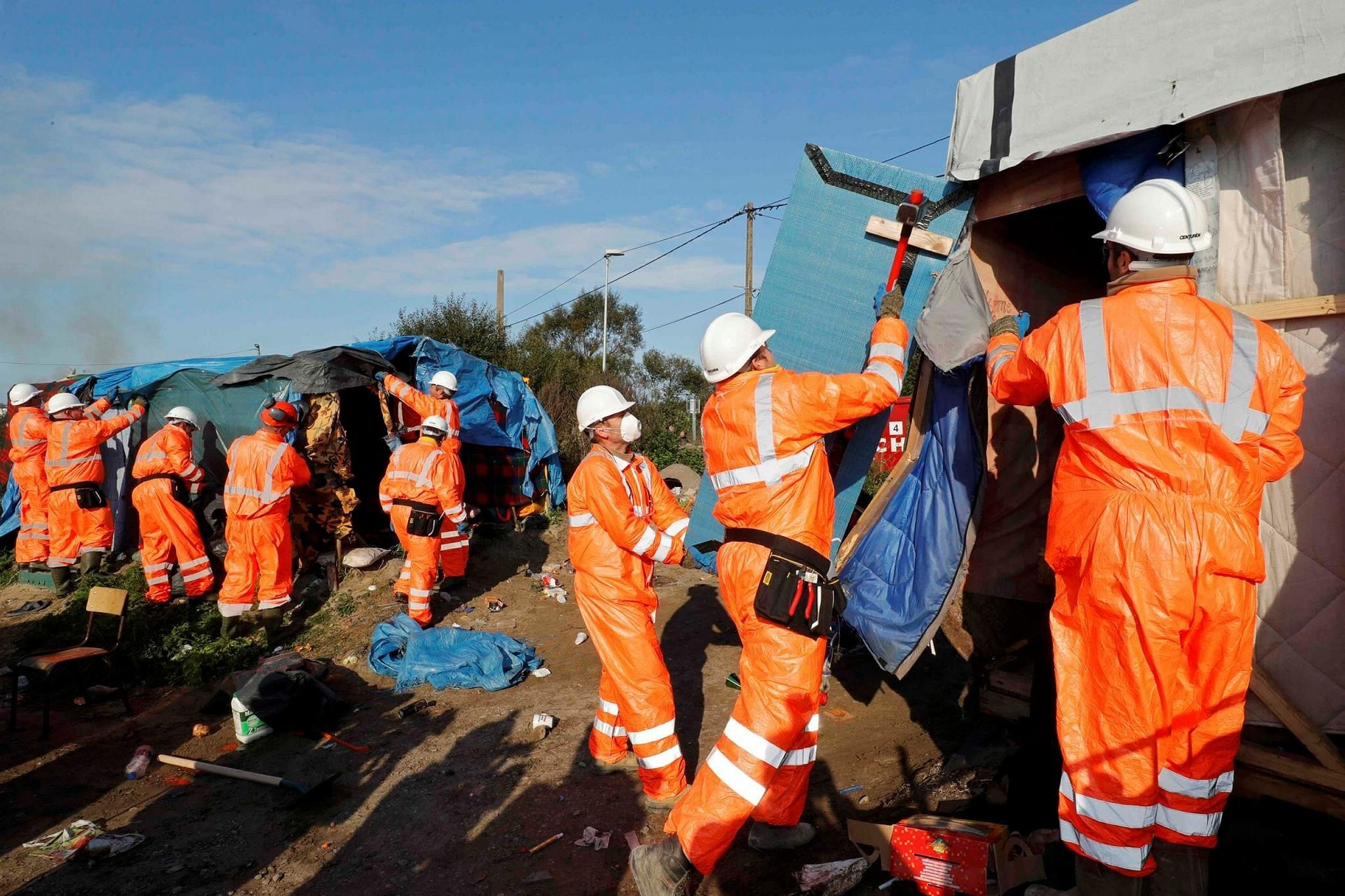 Workmen tear down makeshift shelters on the second day the evacuation of migrants and their transfer to reception centers in France. (Reuters Photo)