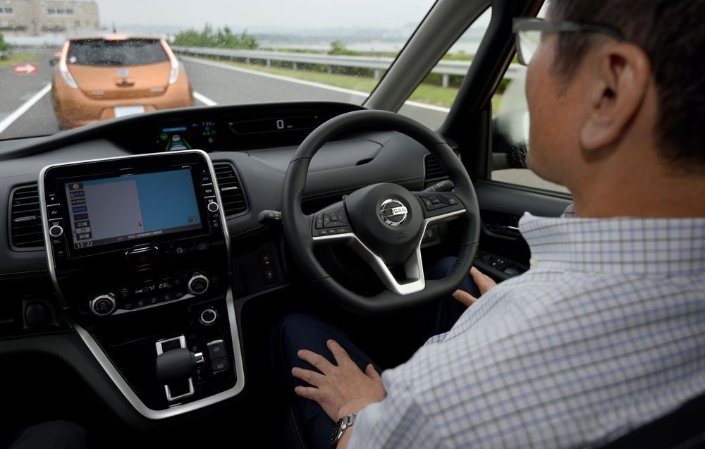 A journalist sitting in the driveru2019s seat of the all-new minivan Serena from Japanese auto giant Nissan Motor takes his hands off the steering wheel during a test drive, at the test course of the companyu2019s Oppama plant in Yokohsuka.