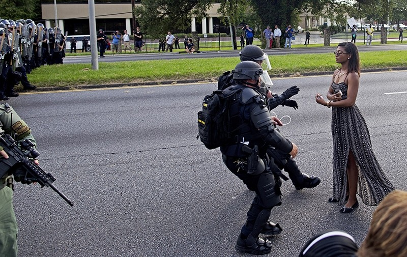 In this Saturday, July 9, 2016 file photo, A protester is grabbed by police officers in riot gear after she refused to leave the motor way in front of the the Baton Rouge Police Department Headquarters in Baton Rouge, La. (AP Photo)