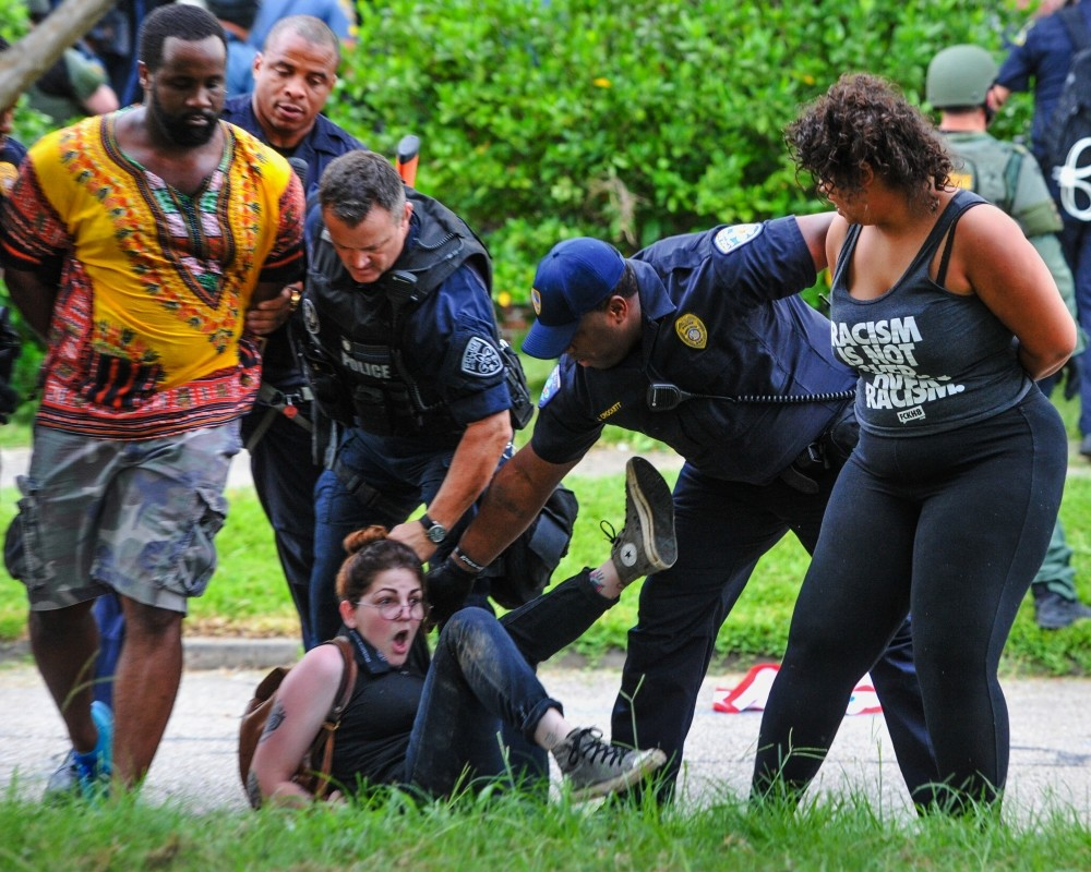 Police detain protesters as they try to clear streets while protesters were gathering against another group of protesters in Baton Rouge, La., July 10.