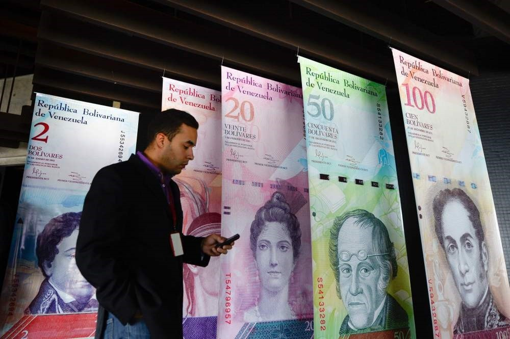 A man walks past banners showing Venezuelau2019s currency, the bolivar, at the Central Bank of Venezuela in Caracas.