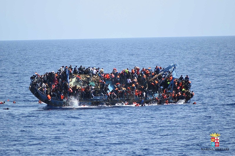 Migrants are seen on a capsizing boat before a rescue operation by Italian navy ships ,Bettica, and ,Bergamini, (unseen) off the coast of Libya in this handout picture released by the Italian Marina Militare on May 25, 2016. (Reuters Photo)