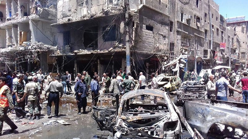 A handout picture released by the official Syrian Arab News Agency (SANA) on June 11, 2016 shows Syrians gathering at the scene of a double bomb attack outside the Sayyida Zeinab shrine (AFP)