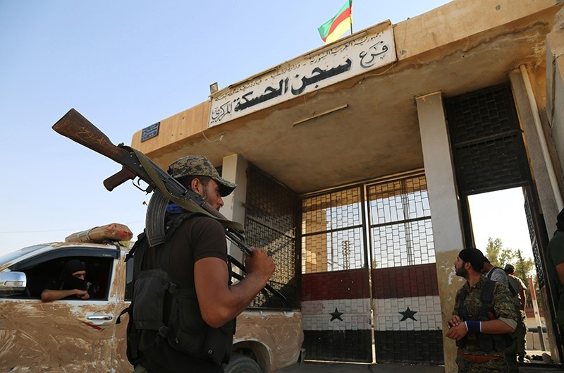 YPG terrorists stand outside the central prison in the northeastern Syrian city of Hasakeh on August 23, 2016 (AFP Photo)