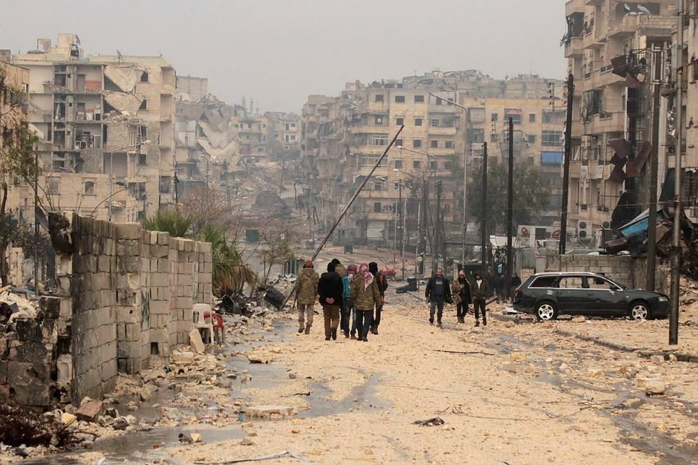 People walk at a damaged area one day after a ceasefire was announced, at al-Mashhad neighborhood in the rebel-held part of Aleppo, Syria, 14 December 2016. (EPA Photo)