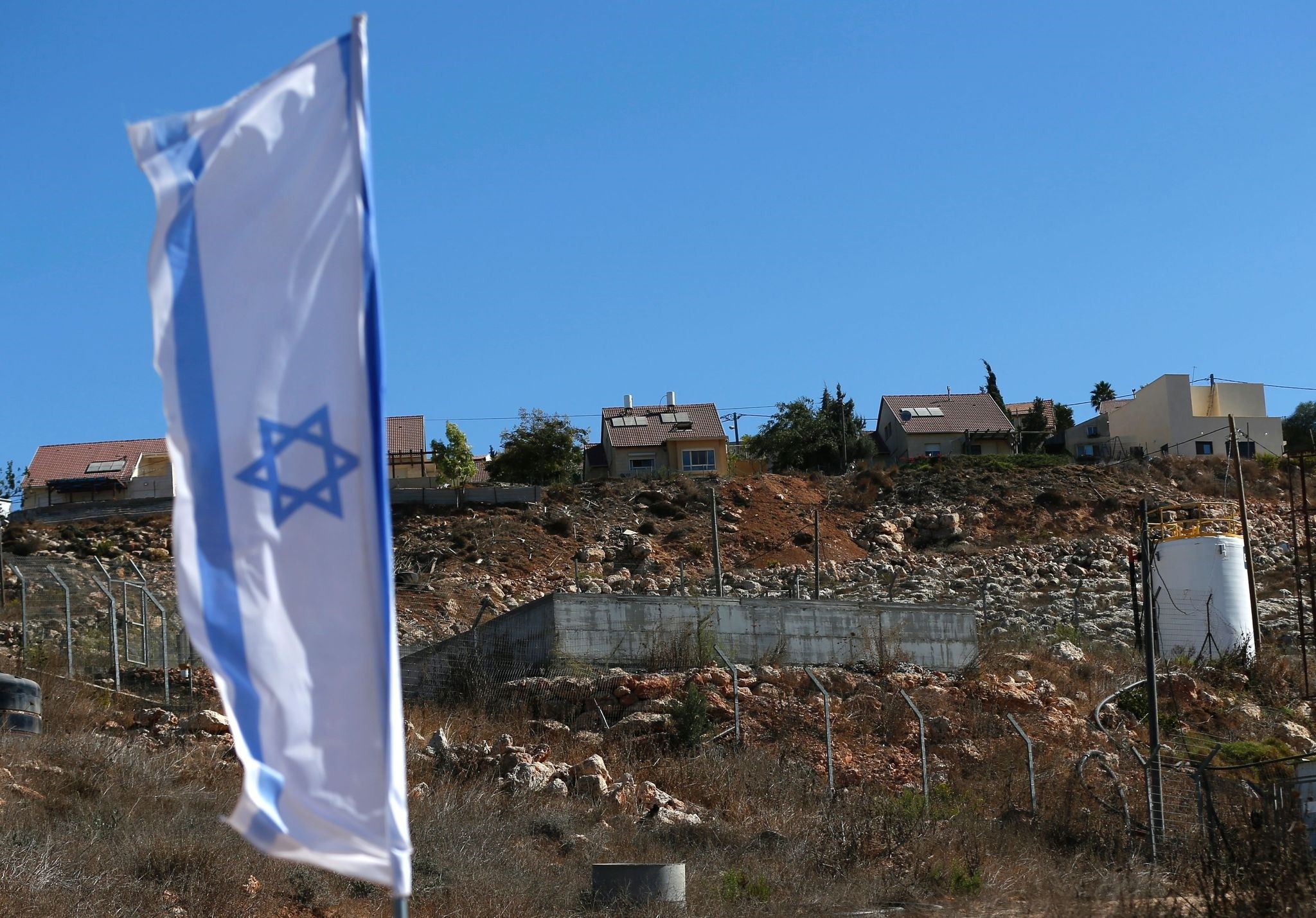 A picture taken on October 2, 2016 shows an Israeli national flag flying next to an Israeli building site of new housing units in the Jewish settlement of Shilo in the occupied Palestinian West Bank. (AFP Photo)