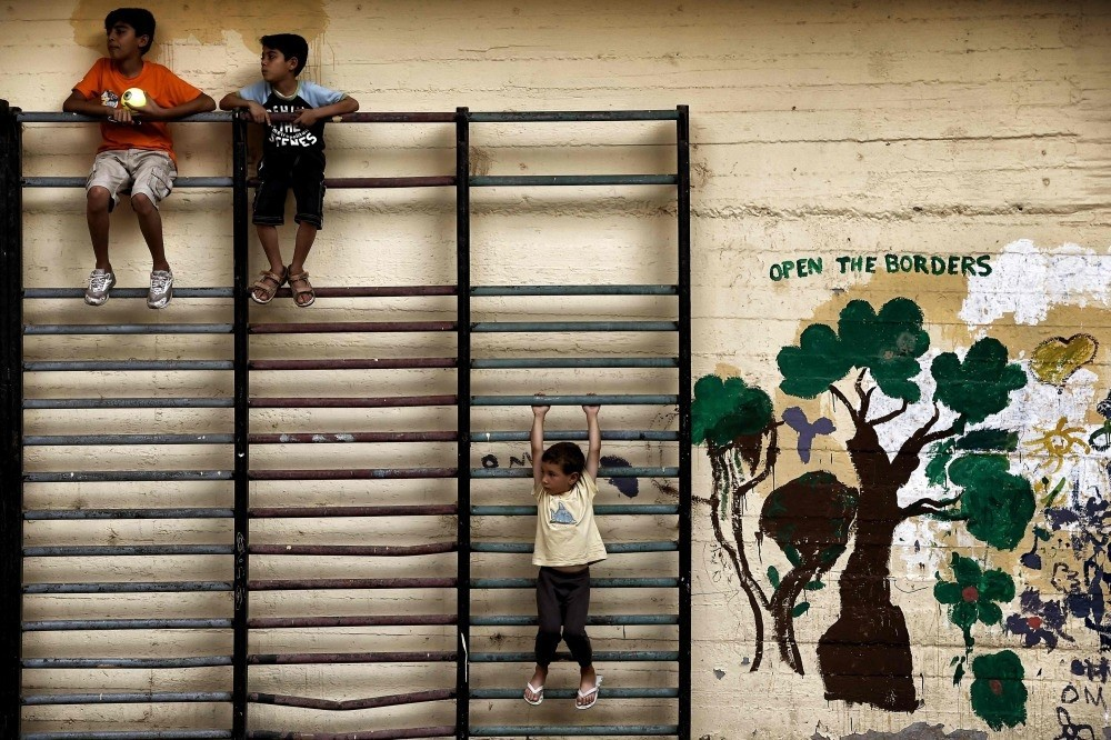 Children playing in the courtyard of an abandoned school used by volunteers for hosting Syrian and Afghan refugees in Athens, July 1, 2016.
