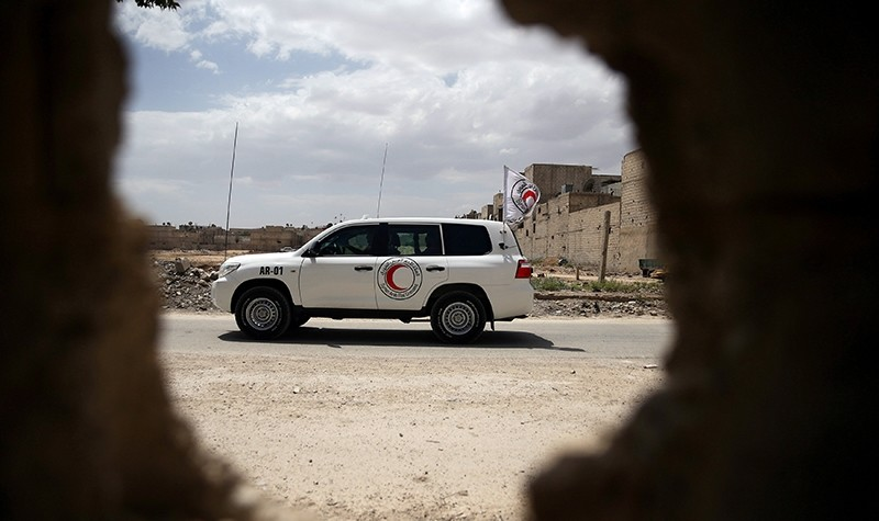 A Red Crescent aid convoy carrying urgent medical supplies is seen through a hole in the wall after its arrival in the rebel held besieged town of Douma (Reuters Photo)
