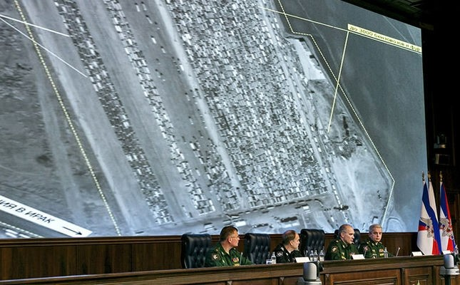 Russian top military officials speak to the media in front of an aerial image which they say is oil trucks near Turkeyu2019s border with Syria is displayed by the Russian Defense Ministry at a briefing in Moscow, Dec. 2, 2015. (AP Photo)