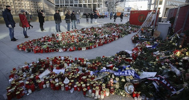 People stand next to flowers and candles in memory of the victims of the terror attack in Berlin, Friday, Jan. 6, 2017 (AP Photo)