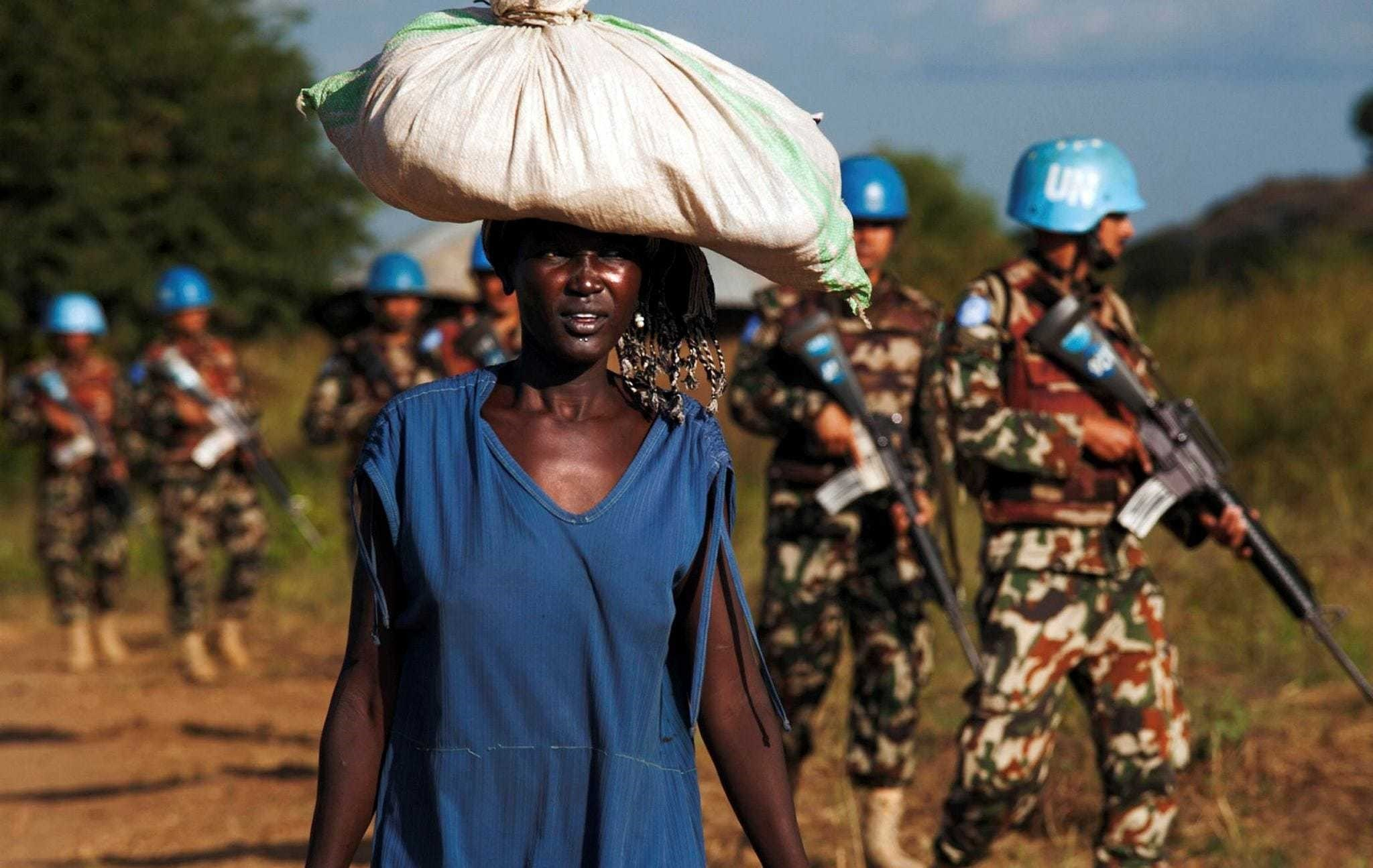 A displaced woman carrying goods as United Nations Mission in South Sudan (UNMISS) peacekeepers patrol outside the premises of the UN Protection of Civilians (PoC) site in Juba.