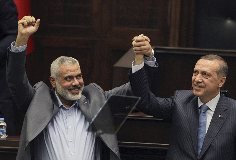 In this Tuesday, Jan. 3, 2012 file photo, Gaza's Hamas Prime Minister Ismail Haniyeh, left, and then Turkish Prime Minister Recep Tayyip Erdogan salute lawmakers in AK Party group meeting (AP Photo)