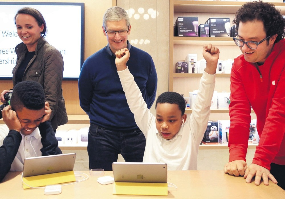 Jaysean Erby raises his hands as he solves a coding problem as Apple CEO Tim Cook watches from behind at an Apple Store, in New York