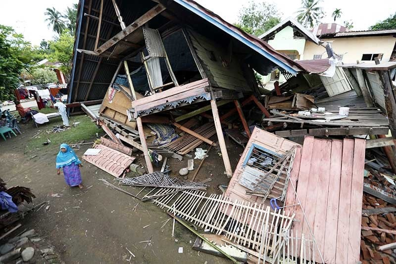 An Acehnese woman passes next to collapsed buildings at Pangwa Village Meureudu, Pidie Jaya after an earthquake struck Pidie Jaya district, Aceh, Indonesia, 09 December 2016. (EPA Photo)