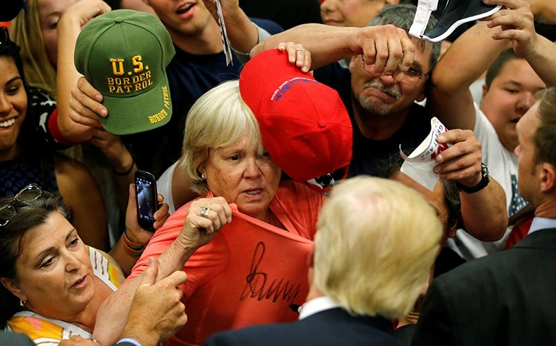 Republican U.S. presidential candidate Donald Trump signs a woman's shirt after a rally with supporters in Albuquerque, New Mexico, U.S. May 24, 2016 (Reuters Photo)