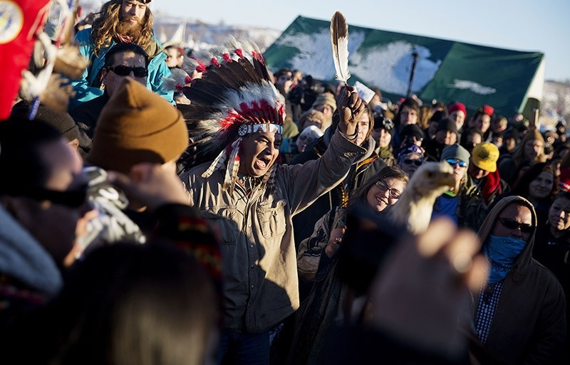 A crowd gathers in celebration at the Oceti Sakowin camp after it was announced that the U.S. Army Corps of Engineers won't grant easement for the Dakota Access oil pipeline in Cannon Ball, N.D., Sunday, Dec. 4, 2016. (AP photo)