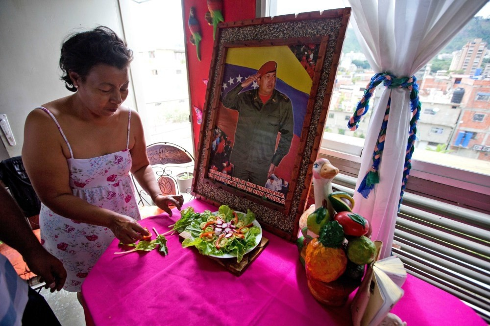 Petra Lezama prepares a salad with vegetables from her roof garden in Caracas, where she keeps a photo of Venezuelau2019s late President Hugo Chavez.