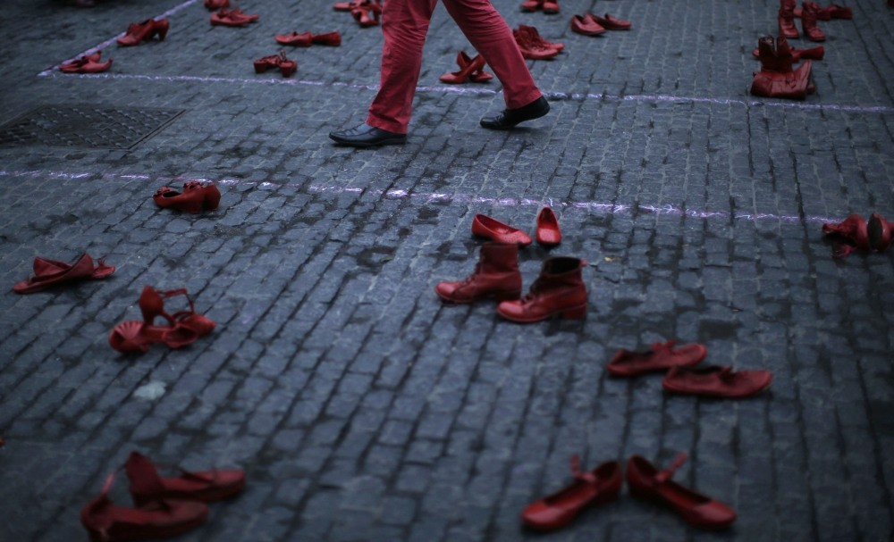 A man walks between red shoes displayed as part of a protest to highlight violence against women at the Sant Jaume square in Barcelona.