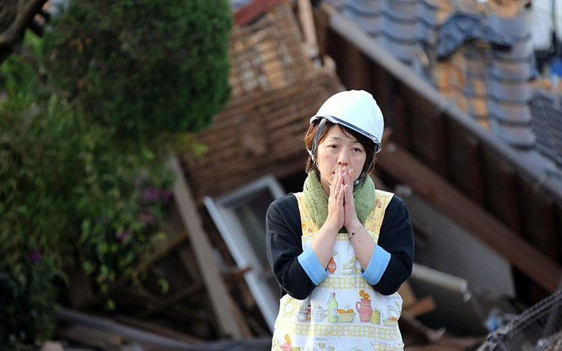 In this Saturday, April 16, 2016, file photo, a resident stands in front of damaged house in Mashiki, Kumamoto prefecture, Japan (AP Photo)