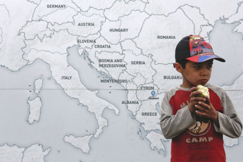 A boy eats an apple next to a map illustrating part of Europe at a makeshift camp for refugees and migrants at the Greek-Macedonian border near the village of Idomeni, Greece.