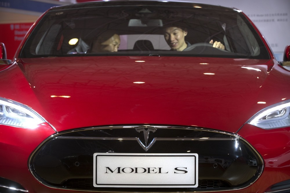A man sits behind the steering wheel of a Tesla Model S electric car on display at the Beijing International Automotive Exhibition.