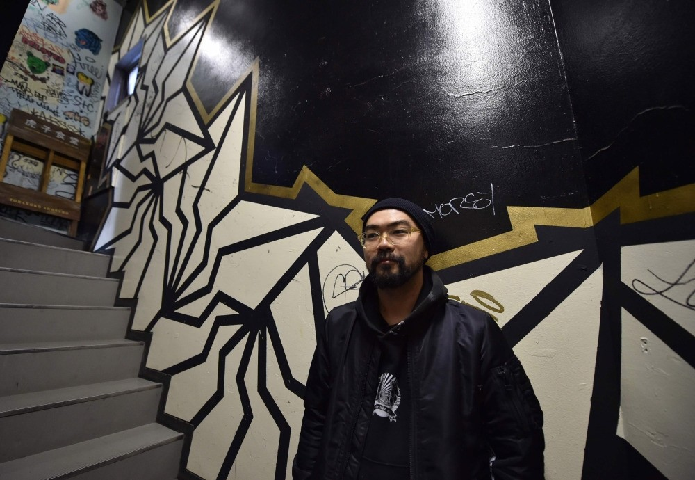 Japanese street artist Kohei Yamao, better known by his nom d'artiste BAKIBAKI, poses with his work in Tokyo.
