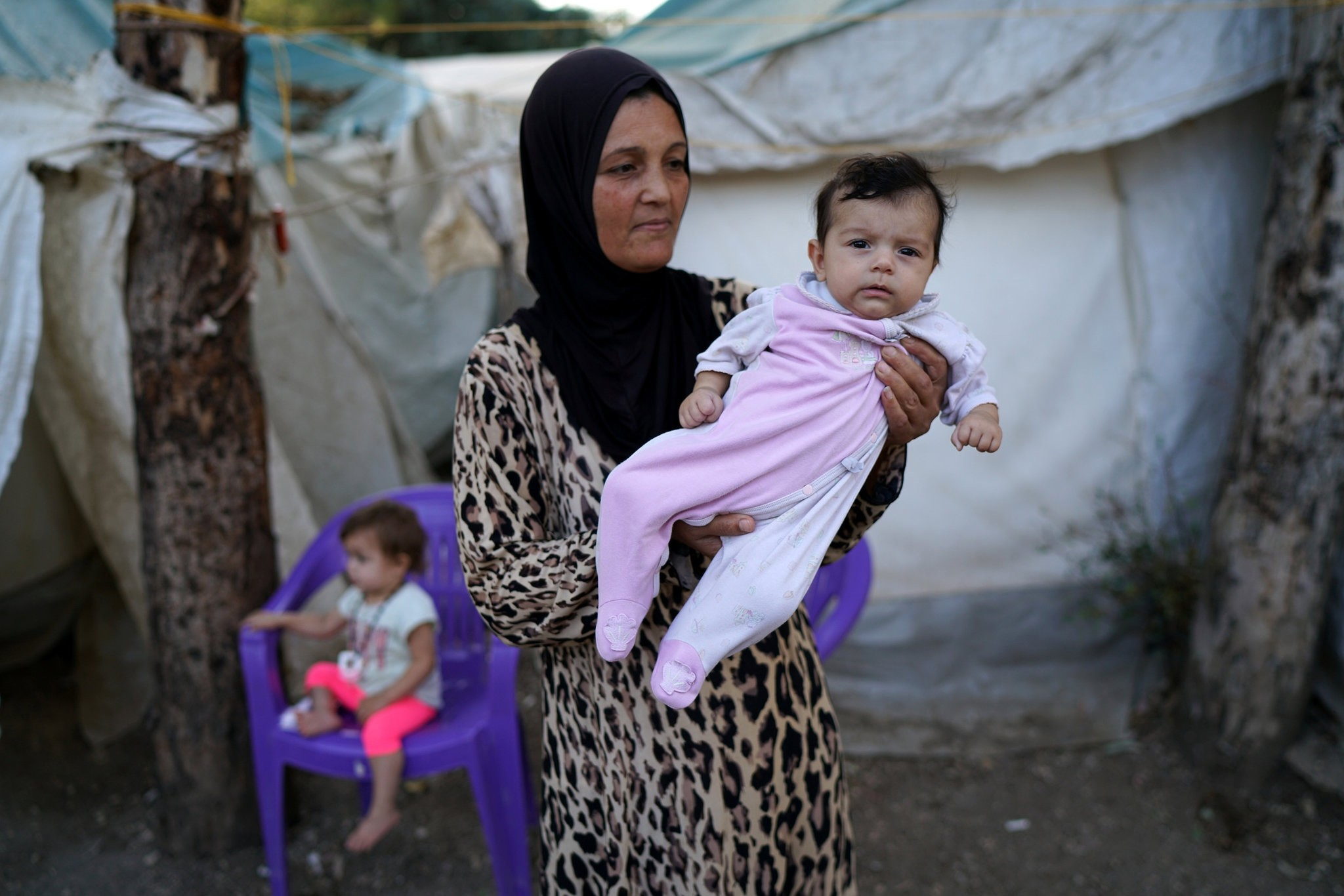 A Syrian refugee mother poses with her baby in front of their tent in Yayladagi refugee camp in Hatay province. (Reuters Photo)