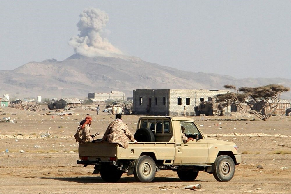 Smoke billows in the distance as Yemeni pro-government forces patrol during clashes against Shiite rebels in Yemen's western Dhubab district on Jan. 9.