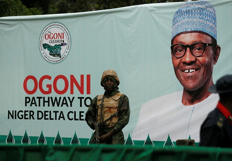 A soldier stands guard in front of a banner with a picture of Nigeria's President Muhammadu Buhari in Gokana, Nigeria on June 2, 2016 (Reuters Photo)