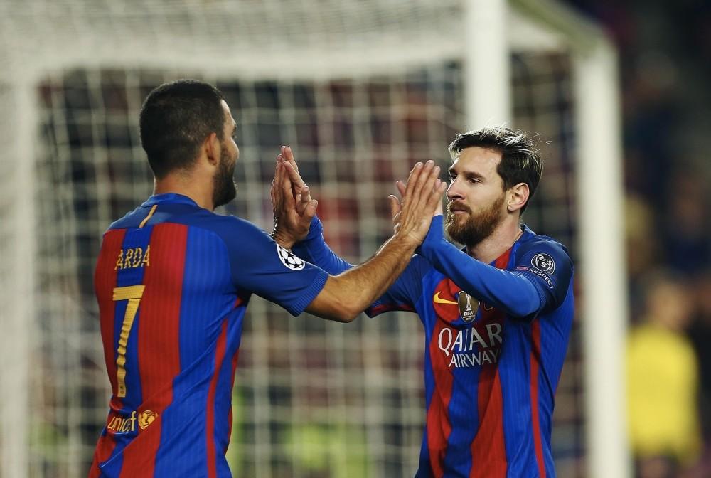 Barcelonau2019s Argentinian striker Lionel Messi (R) celebrates his goal against Borussia Monchengladbach with teammate Arda Turan.