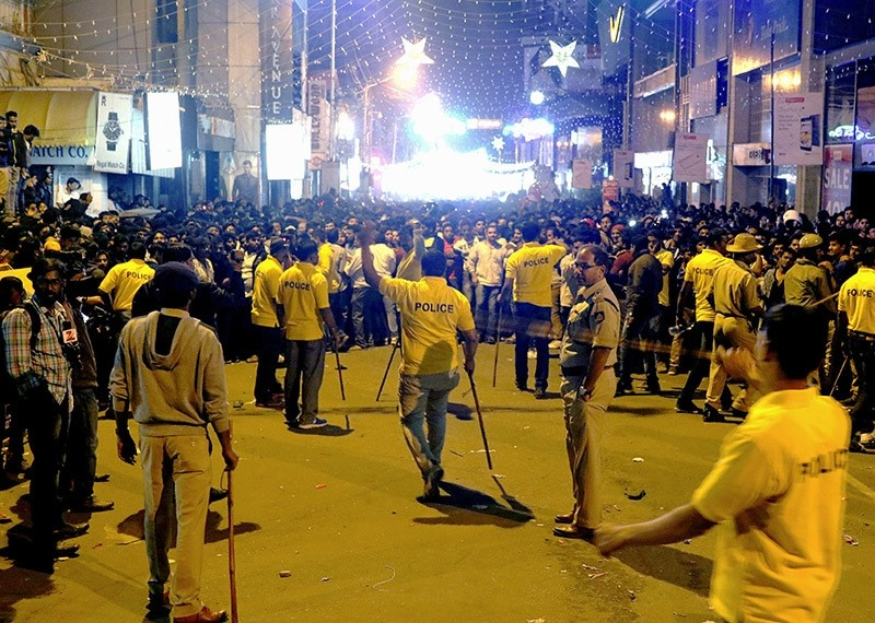 Police personnel hold 'lathi' sticks as they attempt to manage crowds during New Year's Eve celebrations in Bangalore, India. on Jan. 1, 2017. (AFP Photo)
