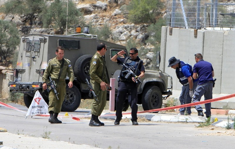 Israeli soldiers and policemen inspect the scene where a Palestinian woman was shot dead by Israeli forces at Ennab Israeli checkpoint near the West Bank city of Tulkarm June 2, 2016.  REUTERS